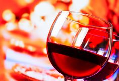 Detail of red wine glasses against unfocused restaurant table background Stock Image
