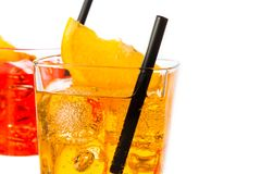 Detail of red and yellow cocktail with orange slice on top and straw isolated on white background Stock Image