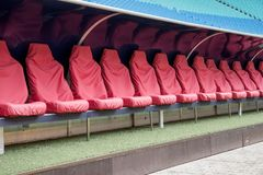 Detail of Reserve chair and staff coach bench in sport stadium. Detail of red Reserve chair and staff coach bench in sport stadium Stock Photos