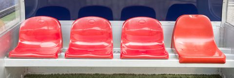 Detail of Reserve chair and staff coach bench in sport stadium. Detail of red Reserve chair and staff coach bench in sport stadium Stock Photo