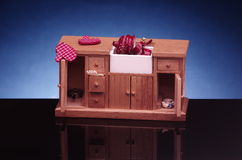 Detail of retro doll house kitchen furniture,cupboard with sink on black and blue background. Detail of retro doll house kitchen furniture,cupboard with sink on stock image