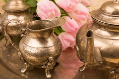 Detail of a retro tea time set. Set with flowers for tea time in metal bronce retro style Royalty Free Stock Photos