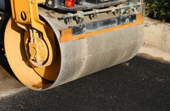 Detail of a road roller with the black asphalt of a street Stock Photo