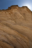 Detail rock layered with blue sky in the background seen from be. Low stock image