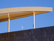 Detail of the Roof of a Modern Office Block. Detail of the wooden finished roof of a Modern Office Block with polished marble walls and the moon against a blue Stock Images