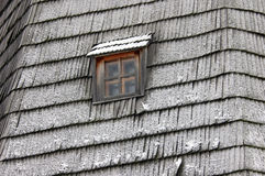 Detail of the roof with a window. WINTER. Fragment of old wooden window with snowy roof Stock Images