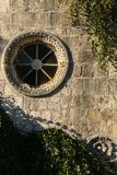 Detail of round window on an antique stone wall - old town Budva stock photos