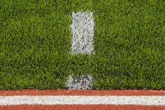Detail of running track rubber lanes with artificial grass. Royalty Free Stock Images