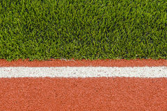 Detail of running track rubber lanes with the artificial grass Stock Image