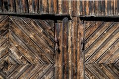 Detail of rustic old wooden barn doors of rough and weathered planks with rusted iron hinge and lock. Antique rural farm house with aged facade of wood and rusty royalty free stock photography