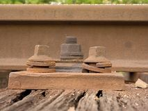 Detail of rusty screws and nut on old railroad track. Rooten wooden tie with rusty nuts and bolts. Stock Photo