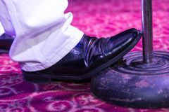 Detail of a salsa singer. Salsa singer detail holding the microphone stand with his foot Royalty Free Stock Photos