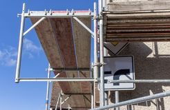 Construction works. Detail of a scaffolding with street sign in front of a blue sky Stock Image