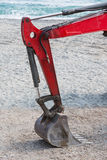 Detail of  scratched excavator's arm with bucket on a beach Stock Photo
