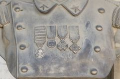 Stone uniform with honour medals. Detail of a sculpture: stone uniform with honour medals Stock Image