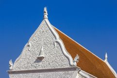 Detail of sculpture on white gable pediment part at Wat Supattanaram Worawihan public thai buddhist temple in Ubon Ratchathani Tha. Iland on blue sky background Stock Photo