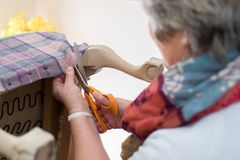 Detail Of Senior Woman Re-Upholstering Chair stock photos