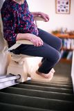 Detail Of Senior Woman Sitting On Stair Lift At Home To Help Mobility. Detail Of Senior Woman Sits On Stair Lift At Home To Help Mobility stock photography