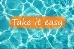 Detail of sentence `Take it easy` on swimming pool water and sun reflecting on the surface Royalty Free Stock Photography