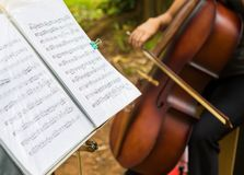Detail of sheet music with cellist in the background Royalty Free Stock Photo