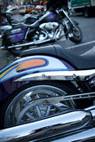 Detail of Shiny Chrome Tailpipe and Rear Wheel of Cruiser Style. Motorycle, as seen at dusk in North Beach, San Francisco, CA. An additional bike is seen in Royalty Free Stock Image