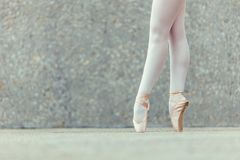 Detail shot of ballet dancer feet. Closeup shot of legs of a female ballet dancer standing on her toes wearing pointe shoes. Ballet dancer practicing dance moves Stock Photography
