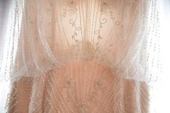 Wedding Dress Detail. Detail shot of a beautiful custom wedding dress hanging on a curtain with strong backlight before a wedding ceremony Stock Photos