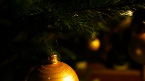 Detail shot glass ball on christmas tree and lit candles, night setting. Concept stock footage