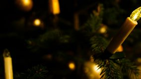 Detail shot glass ball on christmas tree and lit candles, night setting. Concept stock video footage