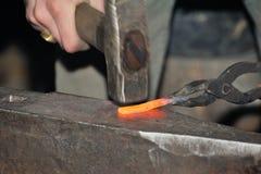 Detail shot of hammer forging hot iron at anvil Royalty Free Stock Photo