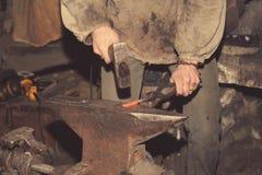 Detail shot of hammer forging hot iron at anvil Stock Image