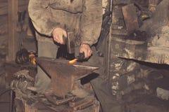 Detail shot of hammer forging hot iron at anvil Stock Photos