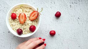 Detail shot of a kitchen table with a white cup of oatmeal and strawberries and a hand that lays strawberries on the. Table. Fruit ingredients concept. Time stock footage
