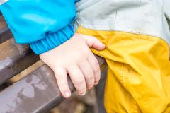 Children cling to a bench and protect themselves with rain pants in wet weather royalty free stock images