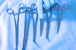 Detail shot of steralized surgery instruments with a hand grabbing  tool Royalty Free Stock Photos