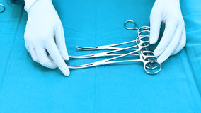Detail shot of steralized surgery instruments with a hand grabbing a tool Royalty Free Stock Photo