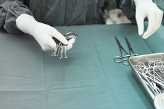 Detail shot of steralized surgery instruments with a hand grabbing a tool Stock Photo