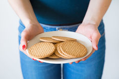 A detail shot of woman's hands with red nails holding a plate of simple delicious cookies, white background. Studio lightning Stock Image