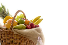Detail from side on a basket full of fresh bio fruit on white background Stock Images