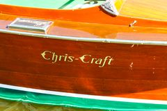 Detail of side of a classic wood Chris-Craft boat with logo painted on wood and water lapping bottom visible at bottom Stock Photos