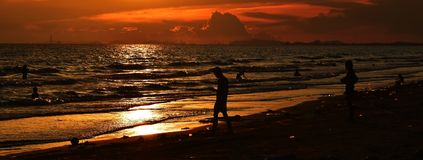 Silhouette of many people on beach and in sea in evening before sunset in holiday. Detail silhouette of many people on beach and in sea in evening before sunset Royalty Free Stock Photos