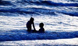 Silhouette of many people on beach and in sea in evening before sunset in holiday. Detail silhouette of many people on beach and in sea in evening before sunset Royalty Free Stock Image