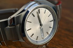 Detail of silver watch with white clock dial on the wooden background as a symbol of time or exactness Stock Images