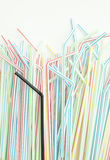 Detail of single black drinking straw into a group of colorful straws Stock Photos
