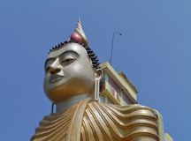 A detail of a sitting Buddha opposite a blue sky Royalty Free Stock Photo