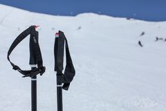 Detail on ski poles hand grip, with blurred piste with skiers an. D deep blue sky in background Stock Image