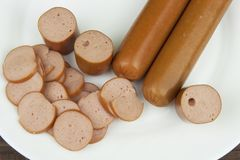 Detail of sliced chicken sausage lying on a porcelain plate. The structure of the poultry sausages. Stock Images