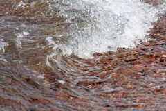 Detail of Small breaking wave at the beach of Aqaba in Jordan, covered with coarse gravel Royalty Free Stock Images