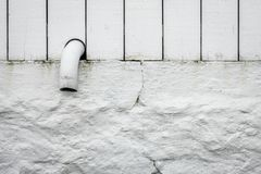 Pipe tip sticking out of a white fence Royalty Free Stock Photo
