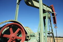 Detail of small scale crude oil pump udner sky Royalty Free Stock Image